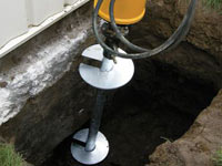 Installing a helical pier system in the earth around a foundation in Green Valley