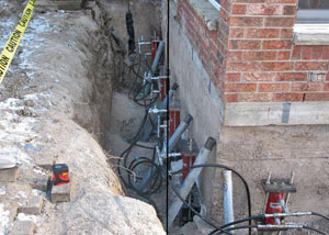 Foundation push piers installed around a house with a foundation settlement issues in Oracle